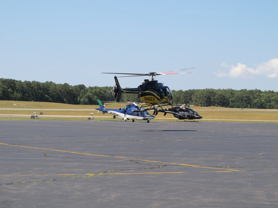 Photo - In this Aug. 20, 2014 photo, a helicopter tales off in front of two other choppers at East Hampton Town Airport. Residents across eastern Long Island are complaining about the noise generated from jets, helicopters and other aircraft that land at the small municipal airport, which is situated in the heart of the summer playground for the rich and famous. (AP Photo/Frank Eltman)