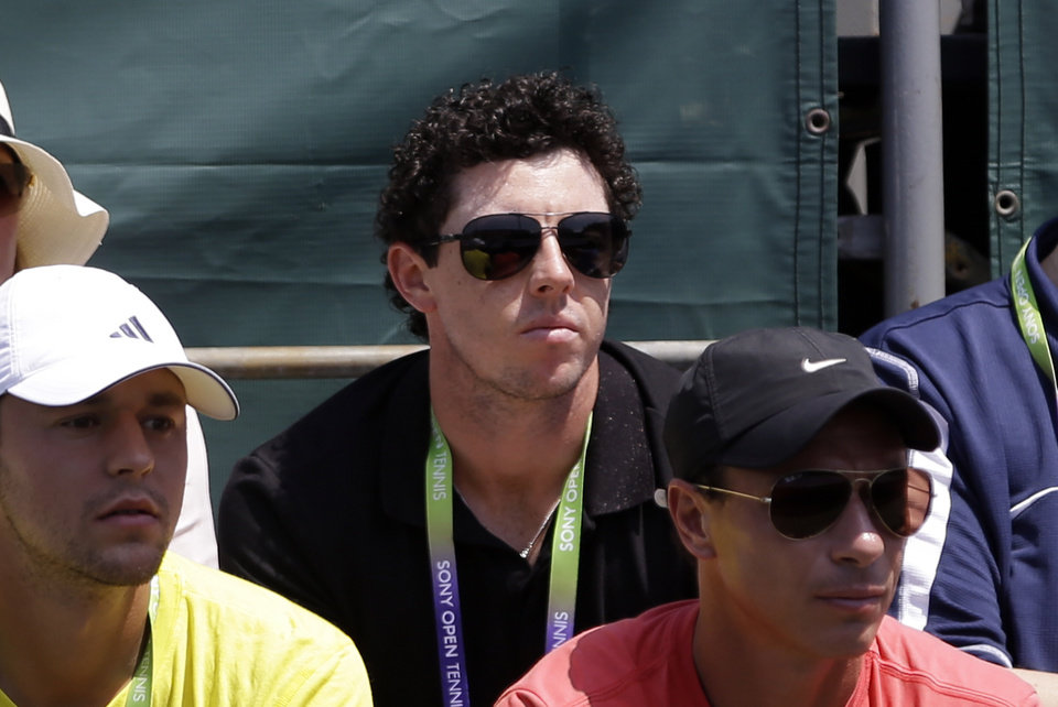 Photo - Golfer Rory McIlroy, center, of Northern Ireland, watches the match between Caroline Wozniacki, of Denmark, and Garbine Muguruza, of Spain, during the Sony Open tennis tournament in Key Biscayne, Fla.,  Saturday, March 23, 2013. (AP Photo/Alan Diaz)