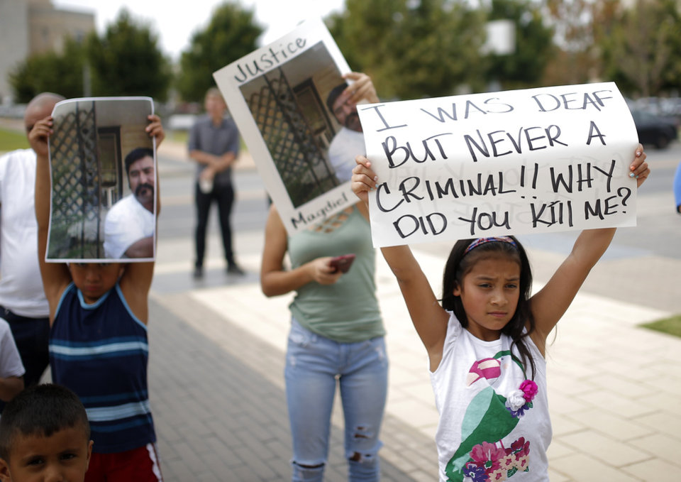 Photo - Protestors hold signs during the Justice for Magdiel Sanchez rally in Oklahoma City, Sunday, Sept. 24, 2017. Photo by Sarah Phipps, The Oklahoman
