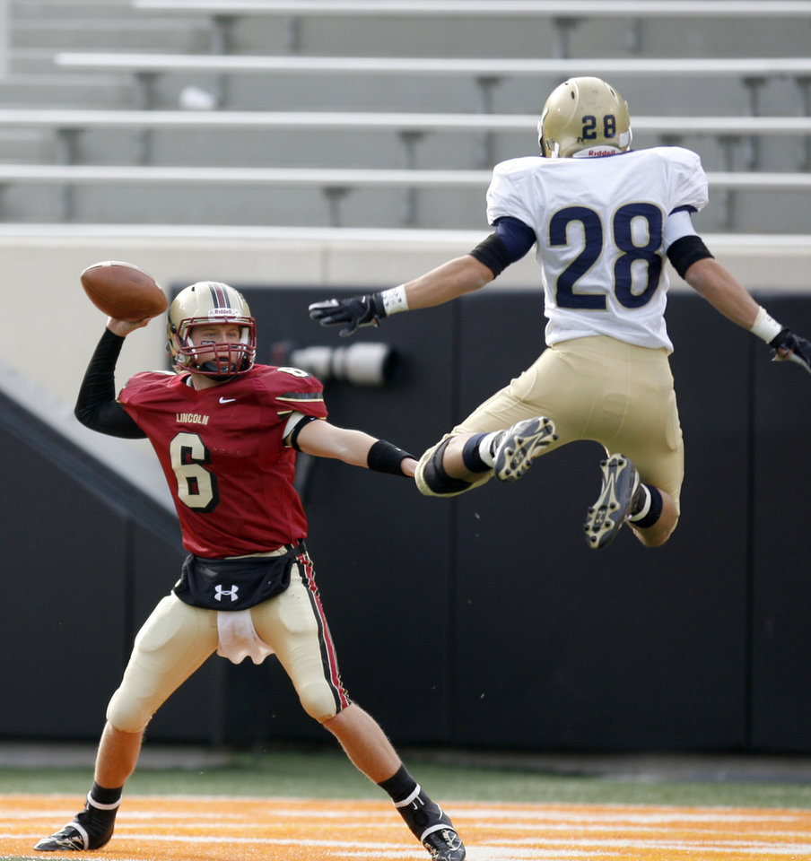Cale Grauer of Lincoln Christian throws a pass by Kingfisher's Jonathan Harvie during the Class 2A high school football state championship game between Kingfisher and Lincoln Christian at Boone Pickens Stadium in Stillwater, Okla., Saturday, December 12, 2009.  Photo by Bryan Terry, The Oklahoman