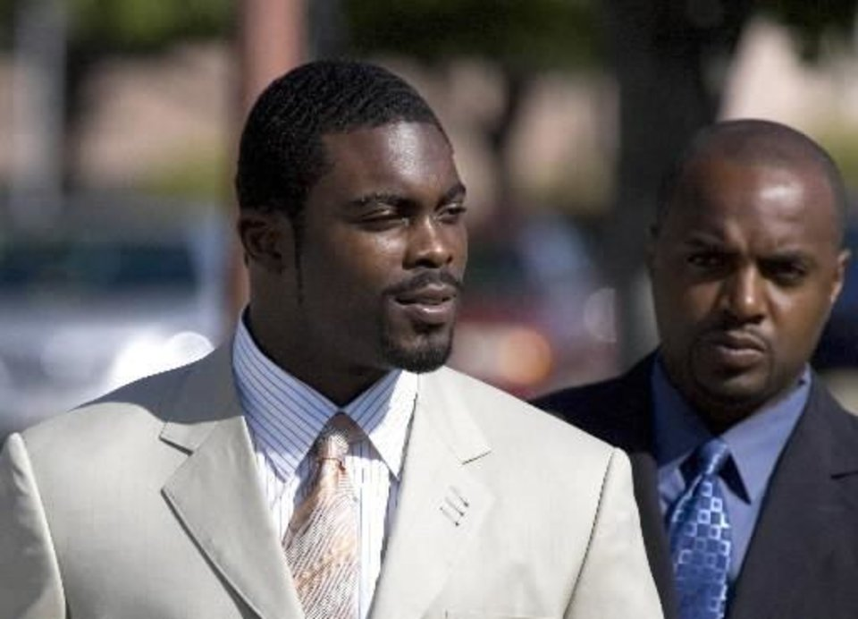 In this July 31, 2009, file photo  Michael  Vick, left, and C.J. Reamon enter U.S. District Court in Newport News, Va.  Vick is back in the NFL, landing a job with the Philadelphia Eagles. (AP Photo/Daily Press, Adrin Snider, File)