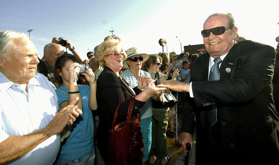 Photo - UNVEILING, DEDICATE, DEDICATION: Actor and former Norman resident James Garner, (R) shakes hands with fan Lu McKenzie (CQ), of Norman, as he walks through the crowd in downtown Norman, Okla. on  Friday, April 21, 2006, where a statue was unveiled in his honor.   By Michael Downes, The Oklahoman