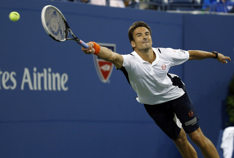 Photo - Tommy Robredo, of Spain, lunges for but can't reach a shot by Nick Kyrgios, of Australia, in their third-round match at the U.S. Open tennis tournament, Saturday, Aug. 30, 2014, in New York. (AP Photo/Elise Amendola)