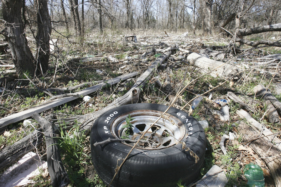 A discarded tire is found among the 2-year-old trash that washed on shore when Arcadia Lake flooded. Equestrian trail riders are upset about the trash.  Photo by PAUL HELLSTERN, THE OKLAHOMAN