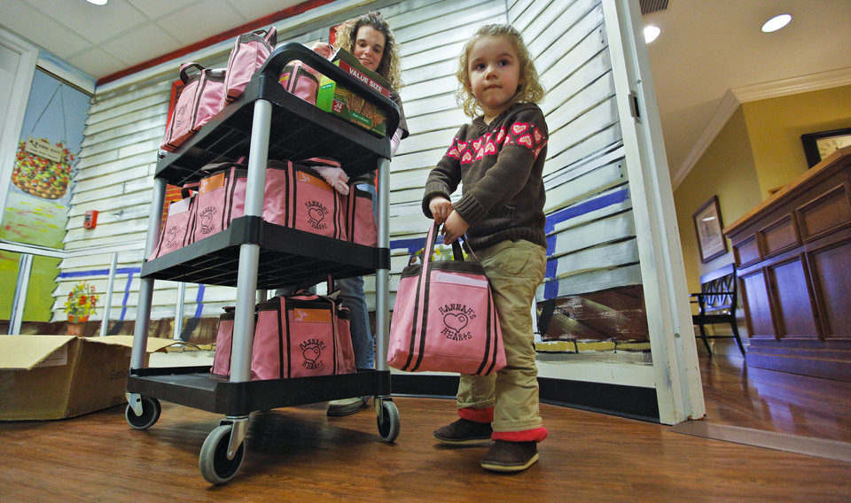 Photo - Hannah Linsky, 3, helps prepare a cart of Hannah's Hearts bags to deliver to families in the neonatal intensive care unit at The Children's Hospital at OU Medical Center.Photos by CHRIS LANDSBERGER, The Oklahoman