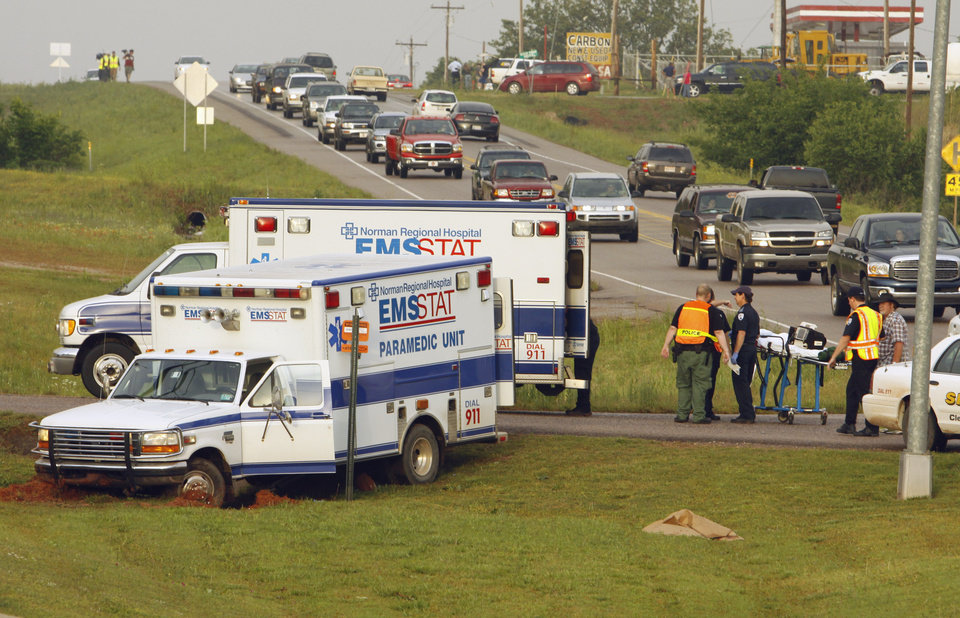 An injured person is transferred to a second ambulance on Highway 9 after the first became stuck in mud following a storm  on Monday, May 10, 2010, in Norman, Okla.  Photo by Steve Sisney, The Oklahoman