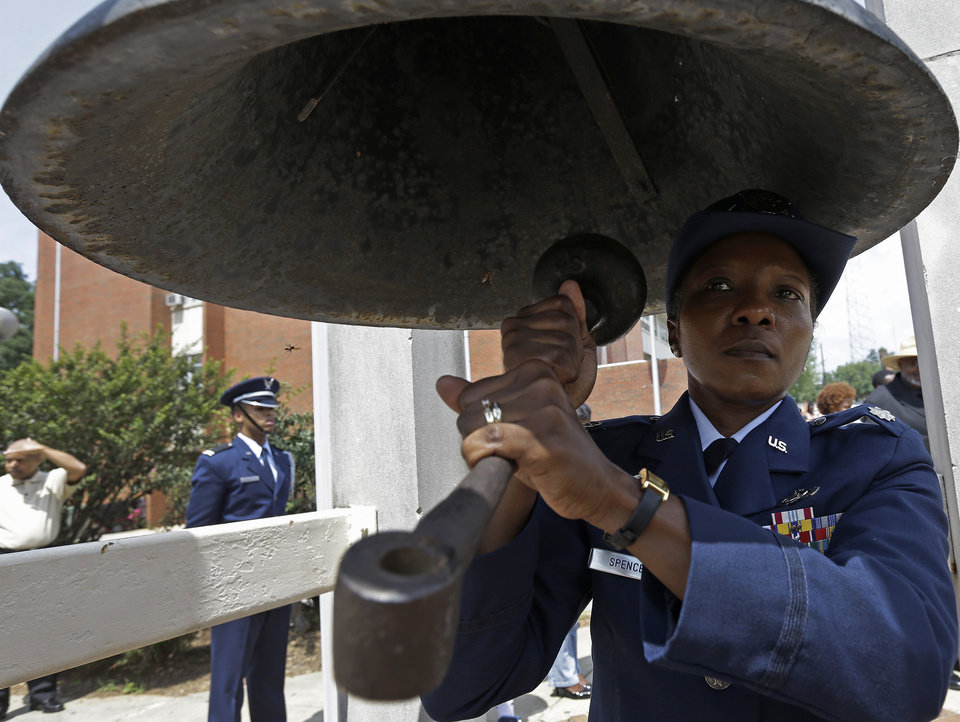 Photo - ROTC Lt. Col. Tangela Spencer rings the bell 50 times as elementary students recite verses from the