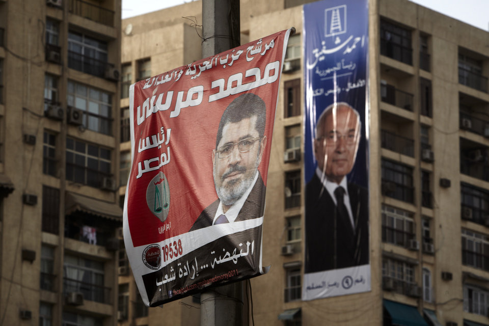 Photo -   Campaign posters supporting presidential candidates Mohammed Morsi, left, and Ahmed Safiq, right, hang in Cairo, Egypt, Monday, May 28, 2012. The runoff vote for Egypt's next president will pit the Muslim Brotherhood's candidate against the last prime minister to serve under Hosni Mubarak, according to full official results released Monday by the election commission. Commission chief Farouq Sultan told a news conference that the Brotherhood's Mohammed Morsi and Ahmed Shafiq, a former air force commander and a longtime friend of the ousted leader, were the top two finishers in the first round of voting held on May 23-24. (AP Photo/Fredrik Persson)