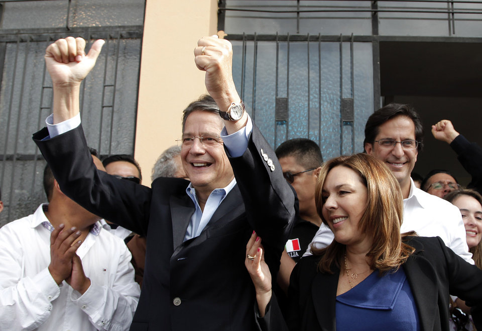 Photo - Presidential candidate Guillermo Lasso of the Creating Opportunities Party ( CREO ), left, gestures to supporters as he stands next to next to his wife Maria de Lourdes Alcivar, second from right,  at a polling station where he accompanied his running mate Juan Carlos Solines, right, to vote in Quito, Ecuador, Sunday, Feb. 17, 2013.  Lasso, a former Banco de Guayaquil executive president,  is the leading opponent to President Rafel Correa who is highly favored to win a second re-election. Ecuadoreans  elect president,  vice-president and National Assembly members Sunday.(AP Photo/Dominique Riofrio)