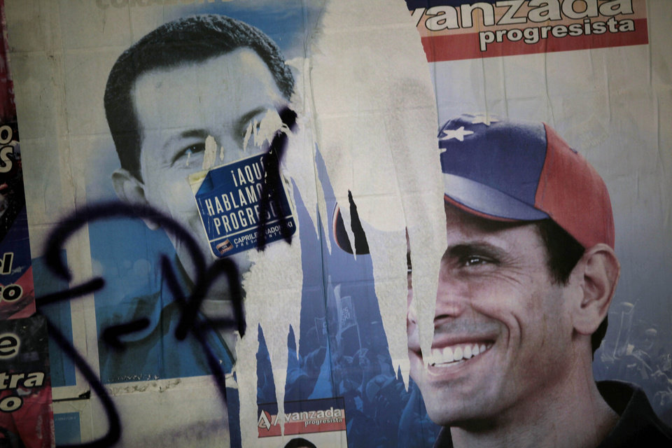 Election campaign posters of presidential candidates, President Hugo Chavez, left, and Henrique Capriles, of the opposition, cover a wall at a polling station during the presidential election in the Catia neighborhood of Caracas, Venezuela, Sunday, Oct. 7, 2012. (AP Photo/Rodrigo Abd)