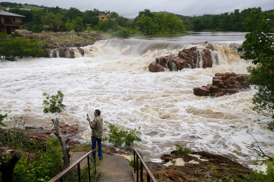 Photo - Eddie Valdez takes pictures of an overflowing Medicine Creek in Medicine Park, Okla., Sunday, May 24, 2015. Photo by Sarah Phipps, The Oklahoman