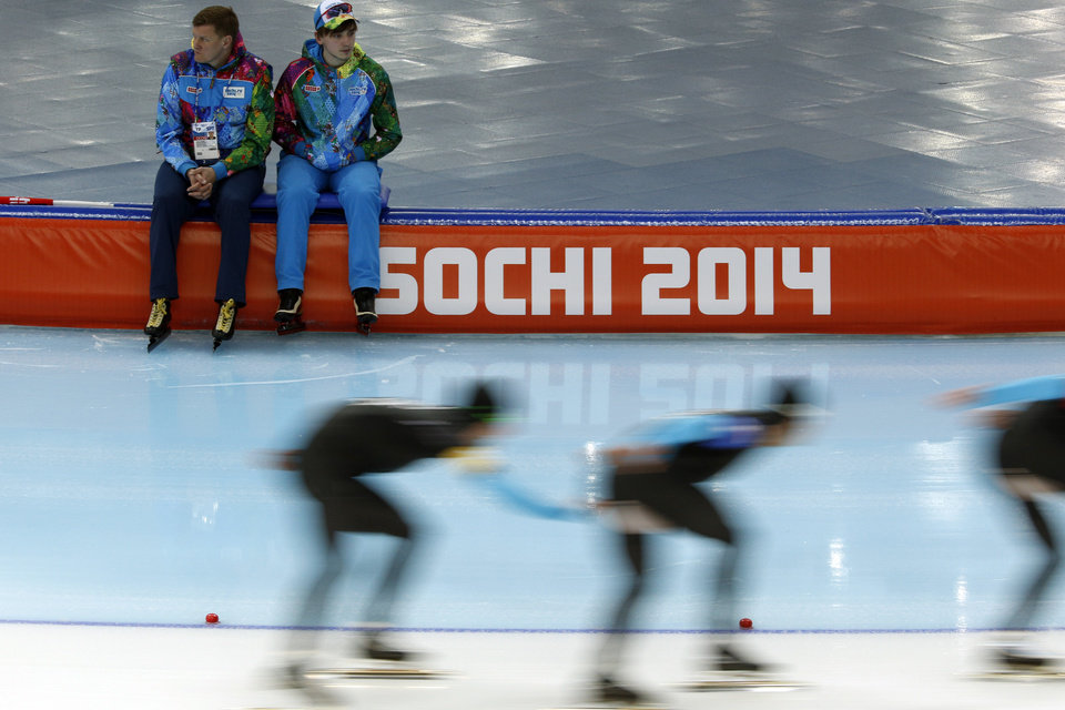 Photo - Volunteers watch speedskaters from the U.S. compete in the team pursuit race for the seventh place at the Adler Arena Skating Center at the 2014 Winter Olympics, Saturday, Feb. 22, 2014, in Sochi, Russia. (AP Photo/Pavel Golovkin)