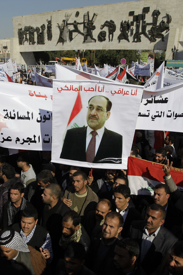 Shiite demonstrators chant pro-government slogans and wave national flags, to show support for Prime Minister Nouri al-Maliki, center in photo on banner, in Baghdad, Iraq, Jan. 12, 2013. Shiite demonstrators are taking to the streets in Iraq\'s capital to show support for the prime minister who has been facing angry protests in Sunni provinces for the past three weeks as the Sunni minority protest what they call discrimination by the Shiite-led government. (AP Photo/Khalid Mohammed)