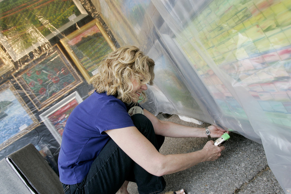 Artist Karen Antos of Addison, TX secures plastic covering over her oil paintings as the threat of rain increased Wed. afternoon Apirl 23, 2008 at the Festival of the Arts in downtown Oklahoma City, Ok. BY JACONNA AGUIRRE/THE OKLAHOMAN.