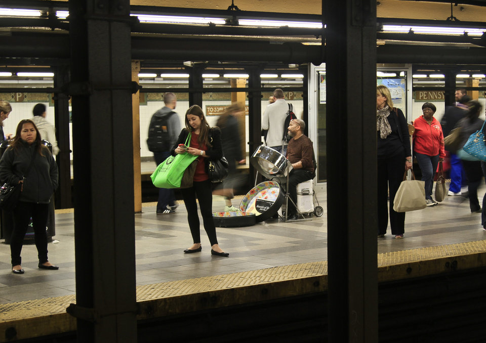 Photo - In this Wednesday, Oct. 9, 2013, photo, Roland Richards, center, plays a steel drum on the 34th Street subway platform in New York. Richards, who immigrated from Trinidad and brought the indigenous pan music, as well, says he is a professional welder by trade.