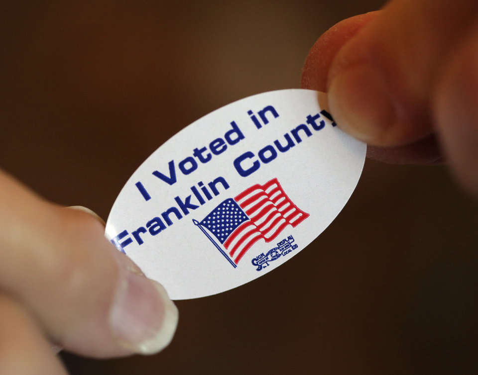 """A voter is handed an """"I Voted"""" sticker after casting her ballot at the old Brown School Tuesday, Nov. 6, 2012, in rural Wellsville, Kan. (AP Photo/Charlie Riedel)"""