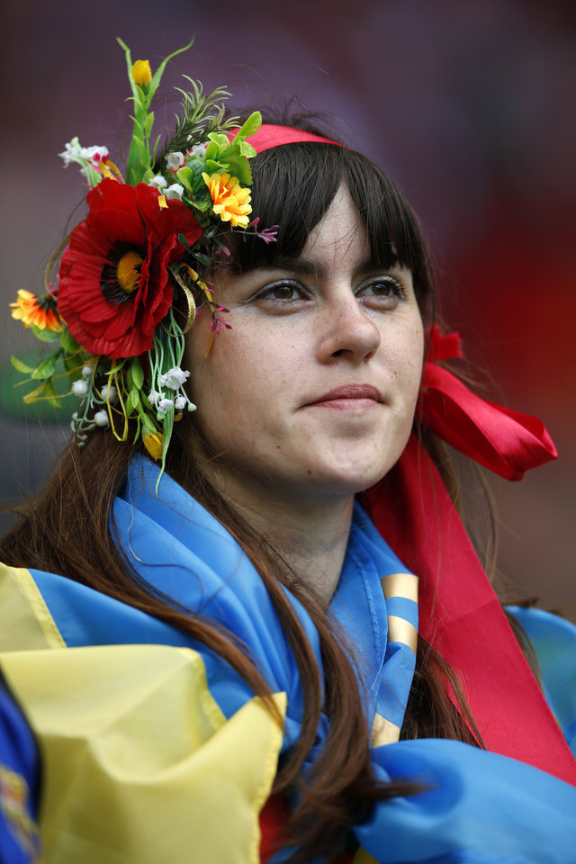 <p>A fan wrapped in the Ukrainian flag wears flowers on her hair on the stands during the Euro 2012 soccer championship Group B match between Denmark and Portugal in Lviv, Ukraine, Wednesday, June 13, 2012. (AP Photo/Armando Franca)</p>