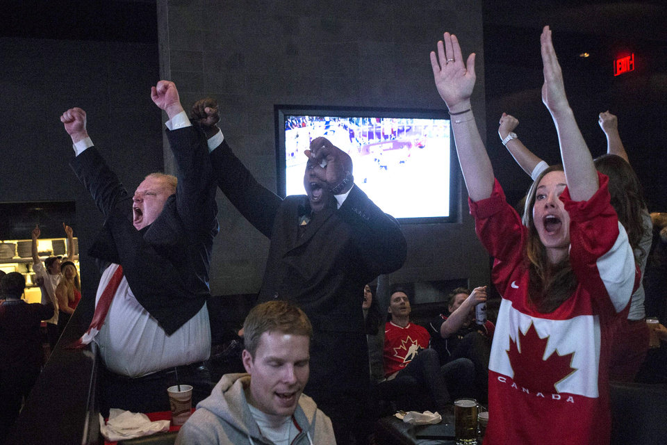 Photo - Toronto Mayor Rob Ford, left, celebrates as Sidney Crosby scores Canada's second goal in the Olympic Hockey final in a Toronto bar on Sunday, February 23, 2014. Canada beat Sweden 3-0 to win the gold medal.  (AP Photo/The Canadian Press, Chris Young)