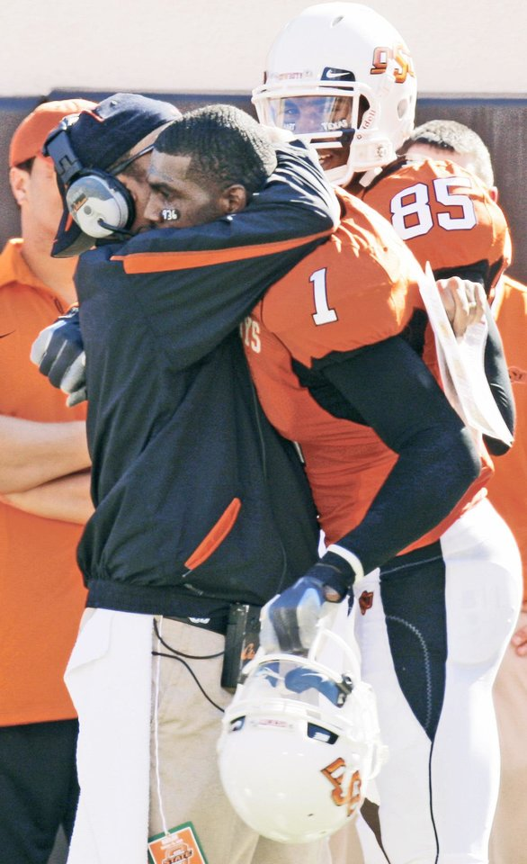 Photo - OSU's Dez Bryant, right, gets a hug from co-offensive coordinator Trooper Taylor during the Cowboys' win over Baylor. Taylor recently left to take a job at Auburn.  PHOTO BY DOUG HOKE, THE OKLAHOMAN
