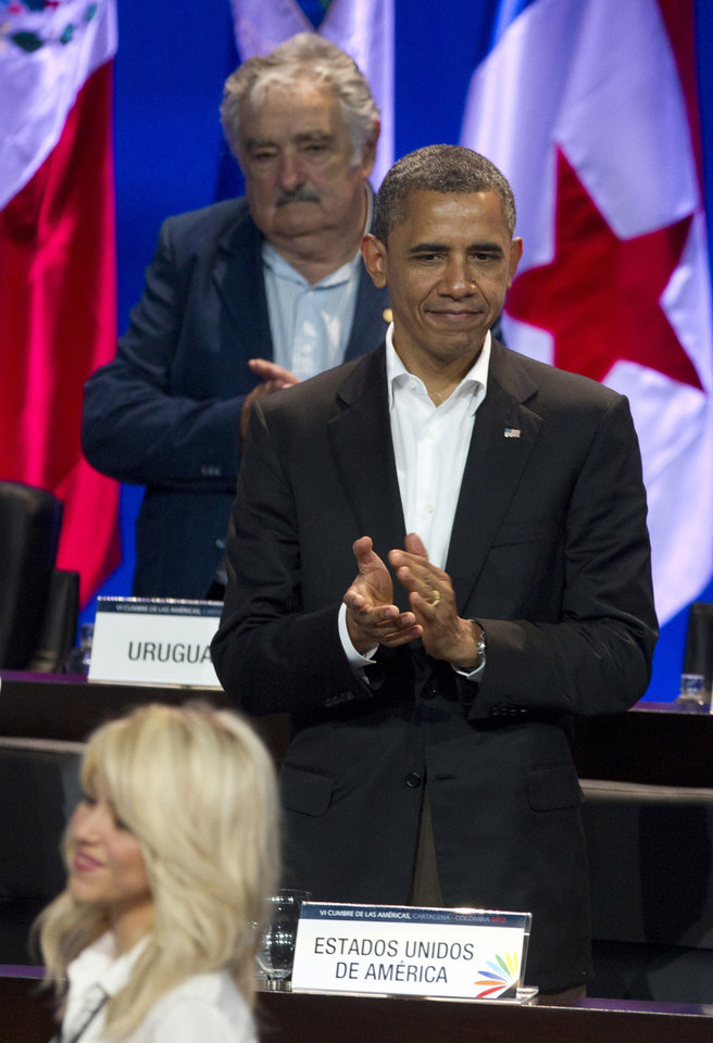 Photo -   President Barack Obama applauds as Colombian singer Shakira arrives, below, as Uruguay's President Jose Mujica stands behind during the arrival ceremony at the sixth Summit of the Americas in Cartagena, Colombia, Saturday April 14, 2012. (AP Photo/Carolyn Kaster)