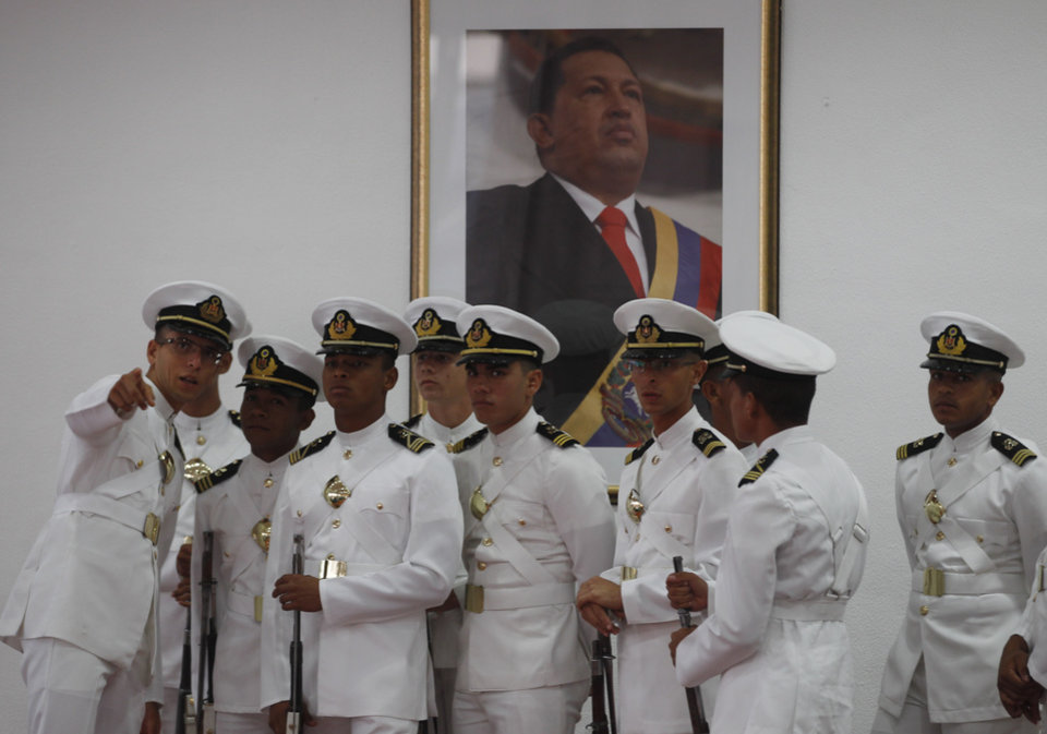 Photo - Members of the guard of honor wait for the arrivals of heads of state that will attend the funeral of Venezuela's late President Hugo Chavez at the airport in Maiquetia, near Caracas, Venezuela, Thursday, March 7, 2013. Chavez died of cancer on Tuesday. (AP Photo/Esteban Felix)