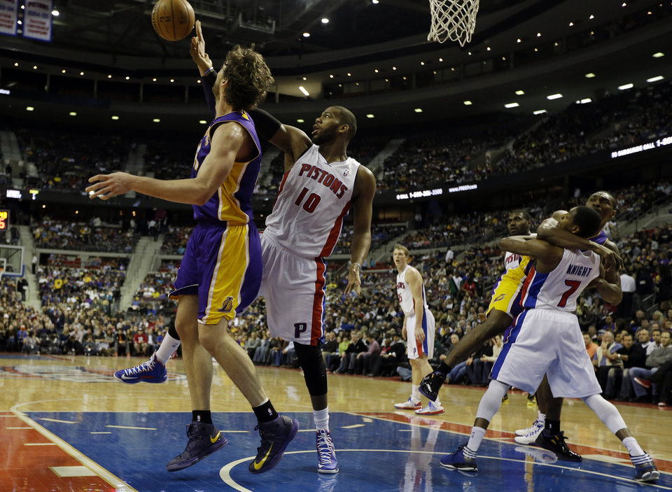 Photo - Detroit Pistons center Greg Monroe (10) fouls Los Angeles Lakers forward Pau Gasol, left, of Spain, as Lakers forward Metta World Peace fouls Pistons guard Brandon Knight (7) during the first quarter of an NBA basketball game at the Palace of Auburn Hills, Mich., Sunday, Feb. 3, 2013. (AP Photo/Carlos Osorio)