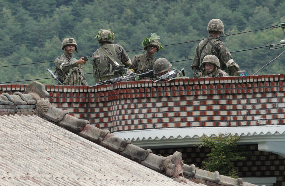 Photo - South Korean army soldiers take position on the roof of a private house to search for a South Korean conscript soldier who is on the run after a shooting incident in Goseong, South Korea, Sunday, June 22, 2014.  The military searched Sunday for an armed South Korean soldier who fled after killing five of his comrades and wounding seven at an outpost near the North Korean border. (AP Photo/Ahn Young-joon)