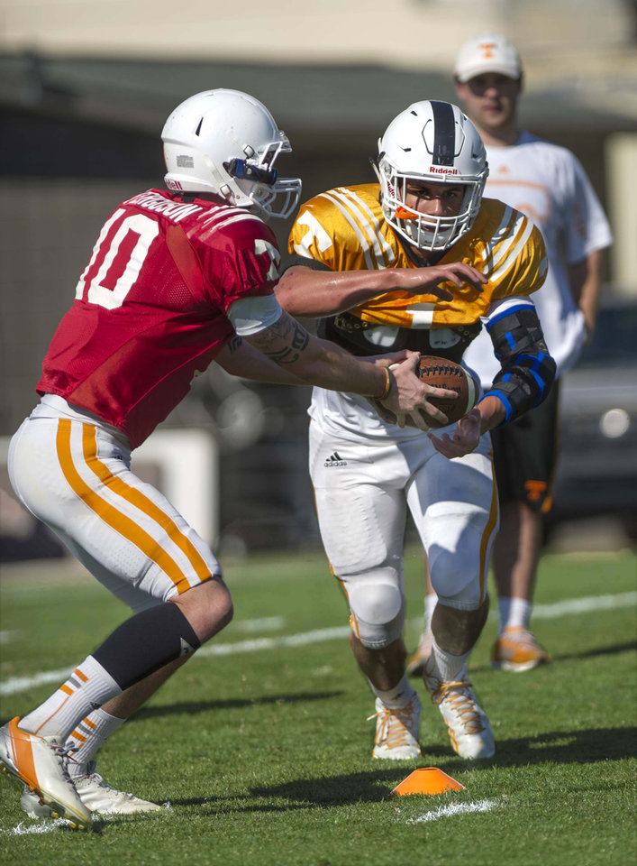 Photo - In this April 1, 2014 photo, Tennessee quarterback Riley Ferguson, left, hands off to running back Jalen Hurd during an NCAA college spring practice in Knoxville, Tenn. Tennessee coach Butch Jones is still waiting for someone to separate themselves from the rest in the Volunteers' four-man quarterback competition as spring practice draws to a close. (AP Photo/The Knoxville News Sentinel, Paul Efird)