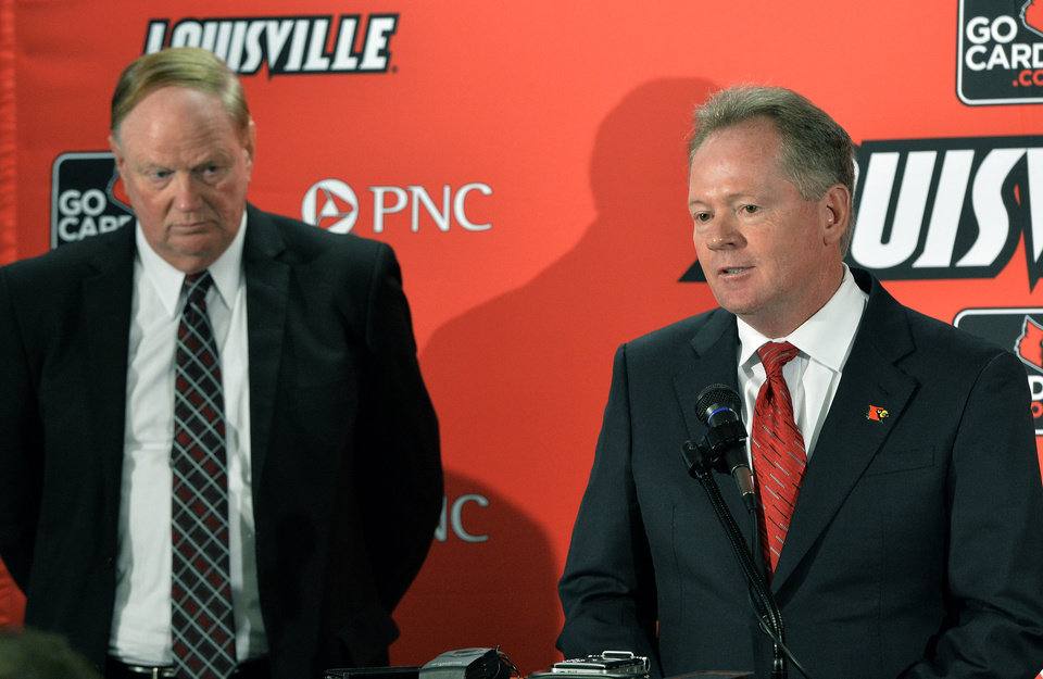 Photo - Bobby Petrino, right, address reporters as University of Louisville President D. James R. Ramsey looks on following the announcement of Petrino's hiring as football coach, Thursday, Jan. 9, 2014, at Papa John's Cardinal Stadium in Louisville, Ky. (AP Photo/Timothy D. Easley)
