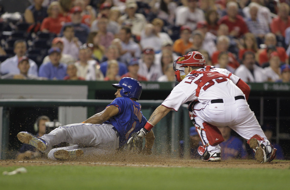 Photo - Washington Nationals catcher Jose Lobaton, right, tags out New York Mets' Chris Young (1) at home plate during the eighth inning of a baseball game, Tuesday, Aug. 5, 2014, in Washington. The Mets won 6-1. (AP Photo/Luis M. Alvarez)