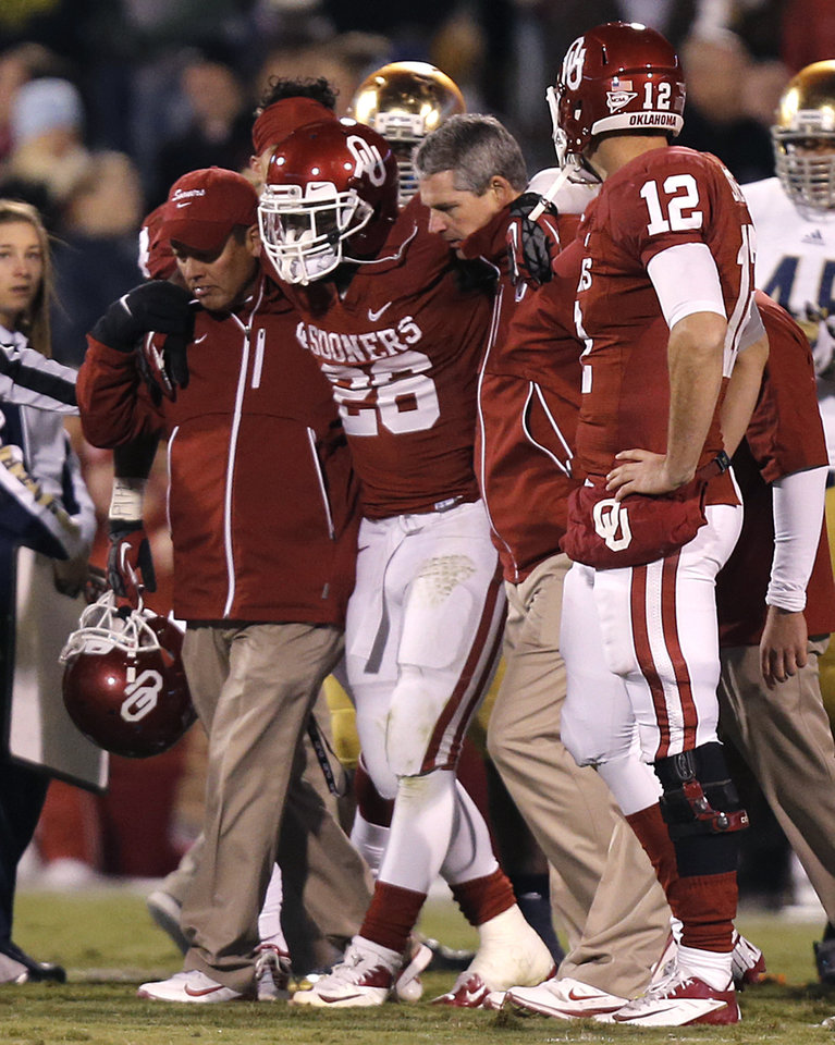 Photo - OU's Damien Williams (26) is carried off the field with an injury during the college football game between the University of Oklahoma Sooners (OU) and the Notre Dame Fighting Irish at the Gaylord Family-Oklahoma Memorial Stadium on Saturday, Oct. 27, 2012, in Norman, Okla. Photo by Chris Landsberger, The Oklahoman