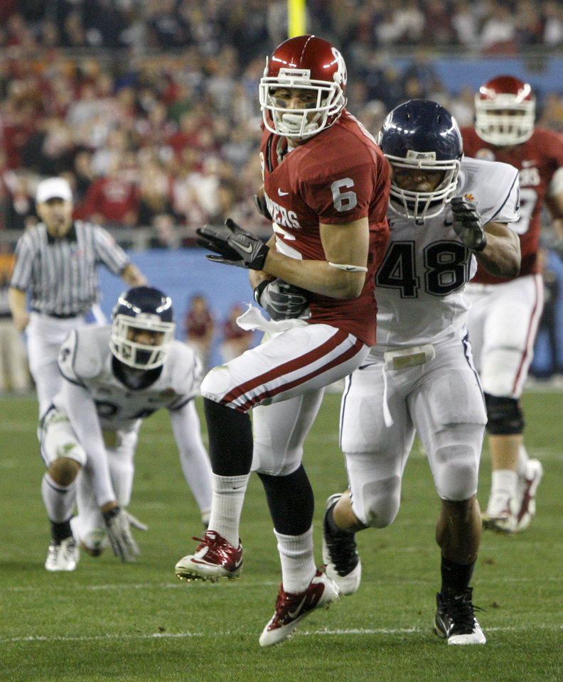 Photo - Oklahoma's Cameron Kenney  (6) is brought down by Connecticut's Trevardo Williams (48) during the Fiesta Bowl college football game between the University of Oklahoma Sooners and the University of Connecticut Huskies in Glendale, Ariz., at the University of Phoenix Stadium on Saturday, Jan. 1, 2011.  Photo by Bryan Terry, The Oklahoman