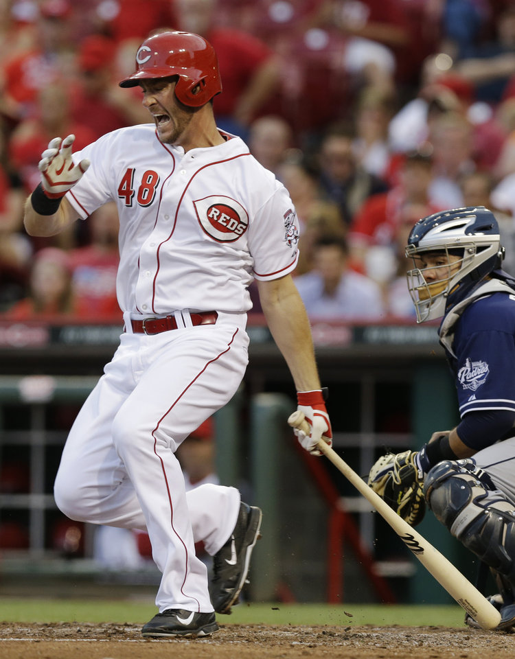 Photo - Cincinnati Reds' Ryan Ludwick hits a foul ball off his foot in the fourth inning of a baseball game against the San Diego Padres, Tuesday, May 13, 2014, in Cincinnati. Rene Rivera catches at right. Ludwick struck out on the at-bat. (AP Photo)