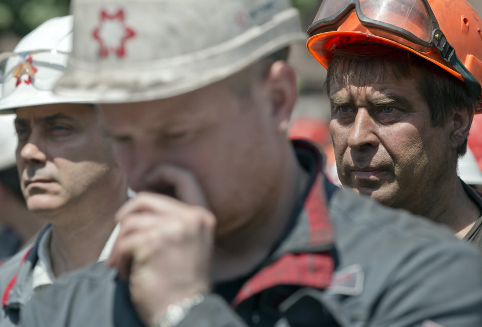 Photo - In this picture taken on Thursday, May 22, 2014, workers of Illich Iron & Steel Works steel plant gather for an anti-war protest, supported by the management, in Mariupol, eastern Ukraine. In the roiling debate over eastern Ukraine, where pro-Russian separatist attacks have turned increasingly bloody, neither the country's richest man nor some of his dirt-poor compatriots have much time for patriotism, ethnic feuding or political parties.  (AP Photo/Vadim Ghirda)