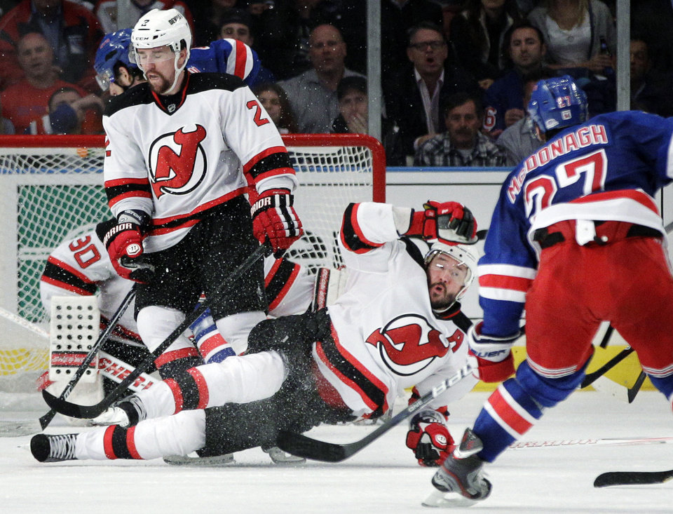 Photo -   New Jersey Devils' Ilya Kovalchuk, of Russia, center, goes down near Marek Zidlicky, of the Czech Republic, left, and New York Rangers' Ryan McDonagh during the third period of Game 5 of an NHL hockey Stanley Cup Eastern Conference final playoff series, Wednesday, May 23, 2012, in New York. The Devils won 5-3. (AP Photo/Frank Franklin II)