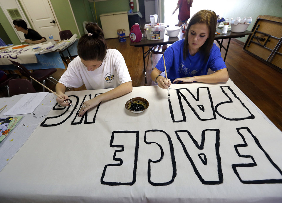 Bishop McGuinness seniors Sarah Tonseth, left, and Mallory Schmidt  create signs for a carnival as part of a senior class community service project at The Sanctuary women's development center in Oklahoma City.  <strong>SARAH PHIPPS - SARAH PHIPPS</strong>