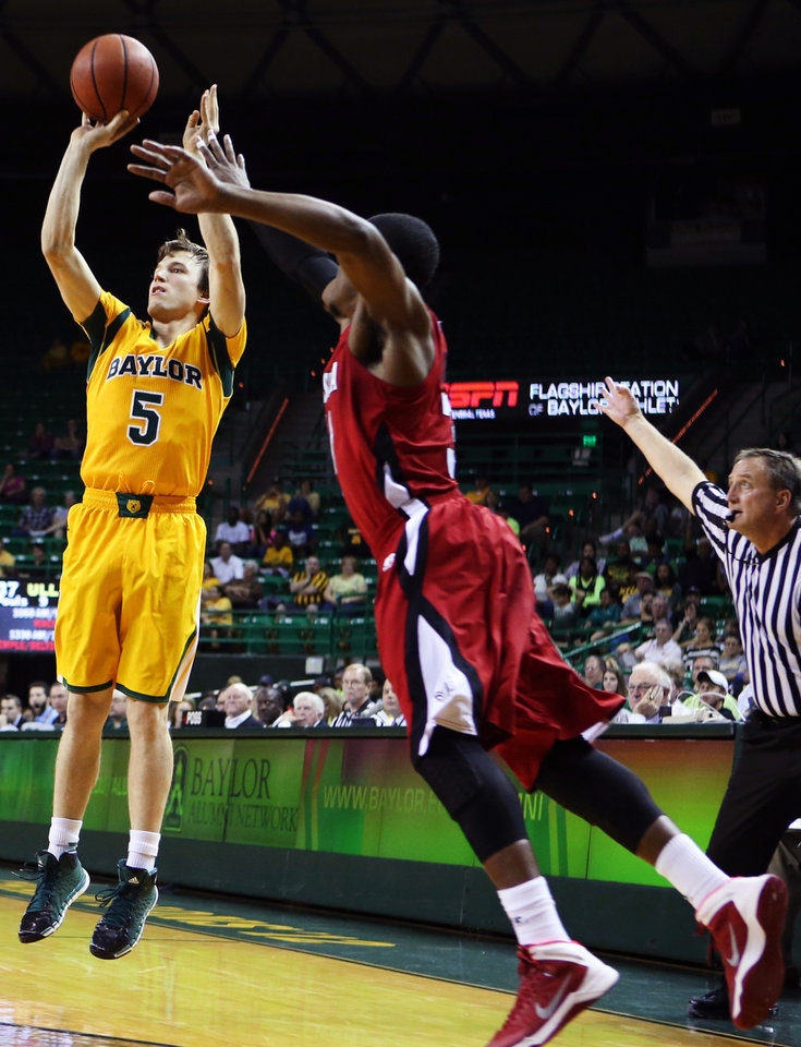 Baylor guard Brady Heslip (5) connects for a three-point shot over Louisiana Lafayette guard Kevin Brown (31), right, in the first half of an NCAA college basketball game, Sunday, Nov. 17, 2013, in Waco, Texas. (AP Photo/Waco Tribune Herald, Rod Aydelotte)