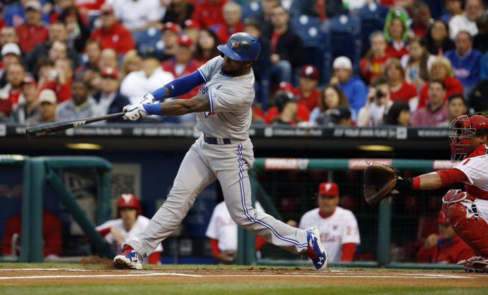 Photo - Toronto Blue Jays' Jose Reyes, left, hits a home run off Philadelphia Phillies starting pitcher Kyle Kendrick as catcher Carlos Ruiz looks on during the first inning of an interleague baseball game, Monday, May 5, 2014, in Philadelphia. (AP Photo/Matt Slocum)