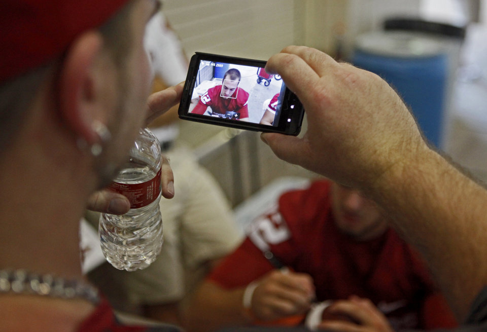 Photo - A fan takes a picture of OU's Landry Jones as he signs autographs during the University of Oklahoma's Meet the Sooners Day at Gaylord Family-Oklahoma Memorial Stadium in Norman, Okla., Saturday, August 6, 2011. Photo by Bryan Terry, The Oklahoman