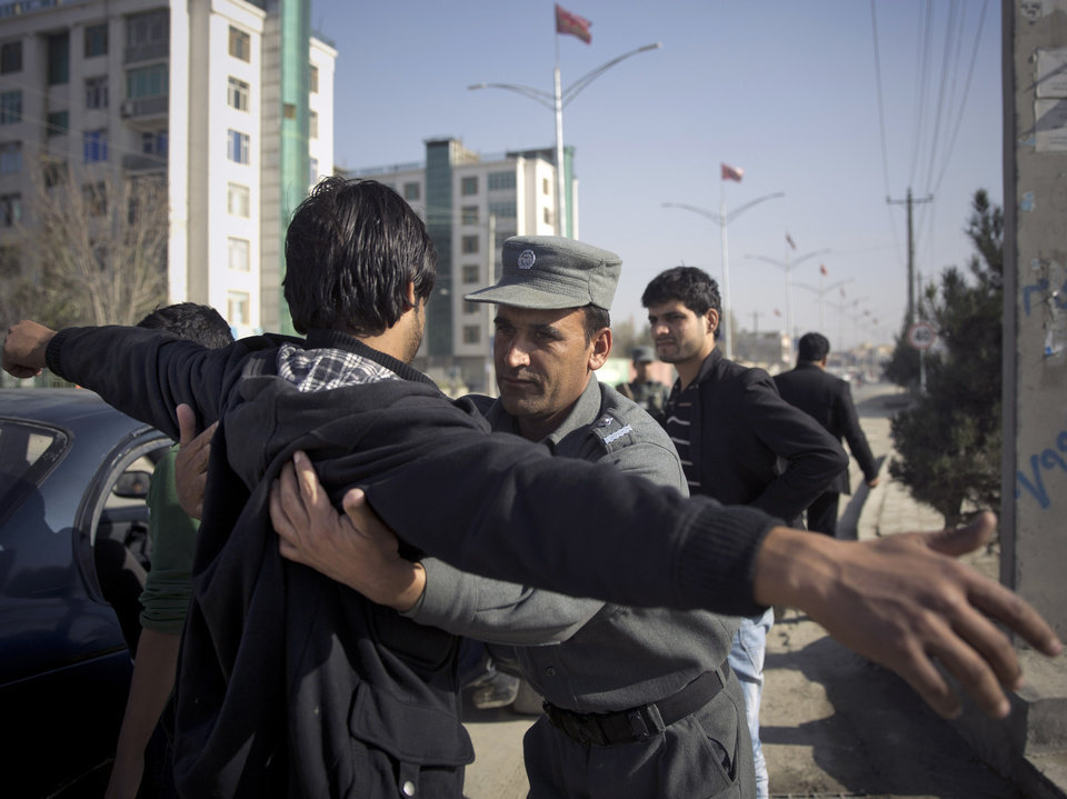 Photo - An Afghan policeman searches men at a checkpoint outside the venue where thousands of prominent Afghans gather to debate a contentious security agreement with the United States in Kabul, Afghanistan, Thursday, Nov. 21, 2013. Afghanistan's president Hamid Karzai said he backs a security deal with the United States but told the gathering of elders that if they and parliament approve the agreement it should be signed after next spring's elections. Without the agreement the United States previously warned that it will remove all its troops by the end of 2014.  (AP Photo/Anja Niedringhaus)