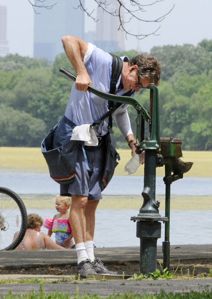 Photo -   Postal carrier Paul Schimke takes a break to pump water into his bottle at an old-fashioned pump along Lake Harriet Friday, July 6, 2012 in Minneapolis where temperatures reached into the upper 90's for another day during the heat wave. The National Weather Service said the record-breaking heat that has baked the nation's midsection for several days was slowly moving into the mid-Atlantic states and Northeast. Excessive-heat warnings remained in place Friday for all of Iowa, Indiana and Illinois as well as much of Wisconsin, Michigan, Missouri, Ohio and Kentucky. (AP Photo/Jim Mone)