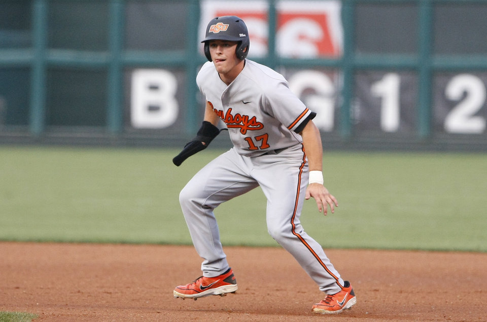 Photo - Oklahoma State center fielder Gage Green leads off of first base in the first inning of a second-round game against Texas in the Big 12 conference NCAA college baseball tournament in Oklahoma City, Thursday, May 22, 2014. (AP Photo/Alonzo Adams)