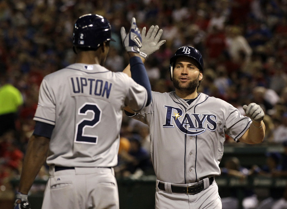 Photo -   Tampa Bay Rays' B.J. Upton (2) congratulates teammate Luke Scott, right, following Scott's solo home run in a pinch-hit appearance off of Texas Rangers relief pitcher Mark Lowe in the sixth inning of a baseball game on Friday, April 27, 2012, in Arlington, Texas. (AP Photo/Tony Gutierrez)