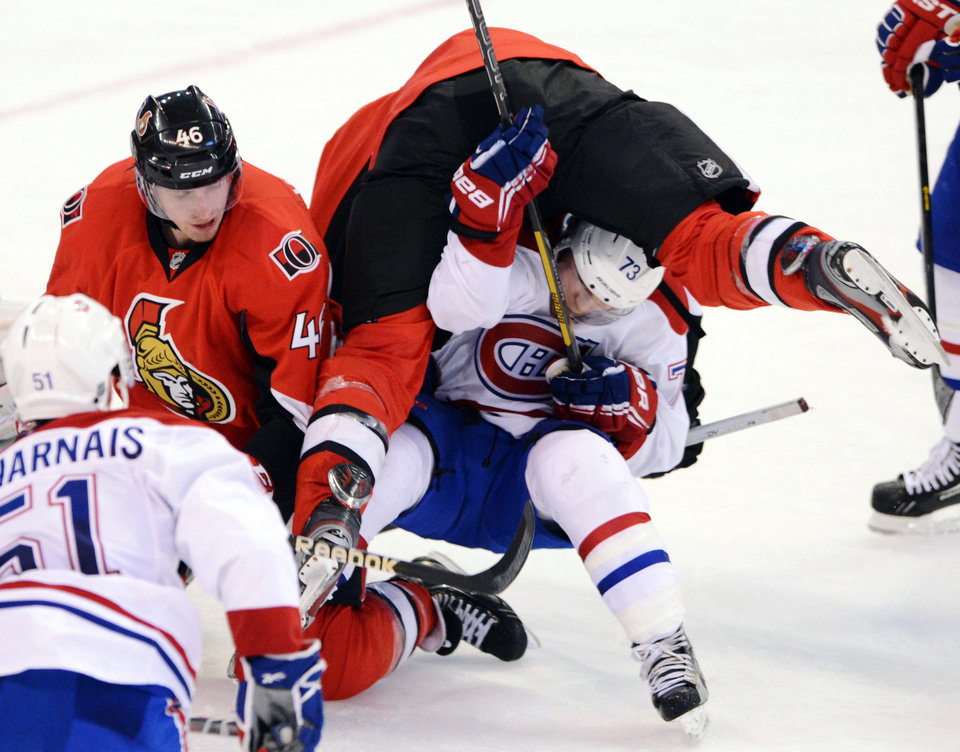 Ottawa Senators' Colin Greening, top, gets flipped over Montreal Canadiens' Brendan Gallagher during the second period of their NHL hockey game, Monday, Feb. 25, 2013, in Ottawa, Ontario. (AP Photo/The Canadian Press, Sean Kilpatrick)