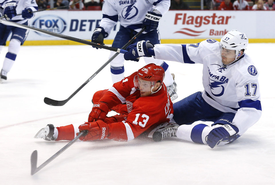 Detroit Red Wings center Pavel Datsyuk (13), of Russia, shoots from the ice as Tampa Bay Lightning center Alex Killorn (17) defends in the second period of an NHL hockey game in Detroit Sunday, Dec. 15, 2013. (AP Photo/Paul Sancya)
