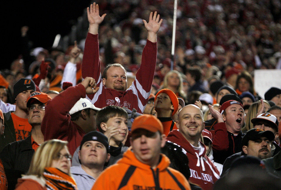 Photo - OU fans celebrate a Sooner touchdown during the Bedlam college football game between the University of Oklahoma Sooners (OU) and the Oklahoma State University Cowboys (OSU) at Boone Pickens Stadium in Stillwater, Okla., Saturday, Nov. 27, 2010. Photo by Sarah Phipps, The Oklahoman