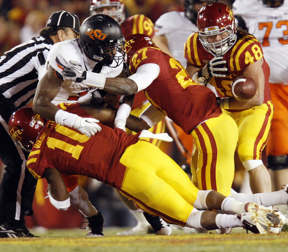 Photo - OSU's Joseph Randle (1) fumbles the ball as ISU's Jacques Washington (10), C.J. Morgan (27) and Jake Lattimer (48) defend in the first quarter during a college football game between the Oklahoma State University Cowboys (OSU) and the Iowa State University Cyclones (ISU) at Jack Trice Stadium in Ames, Iowa, Friday, Nov. 18, 2011. Photo by Nate Billings, The Oklahoman