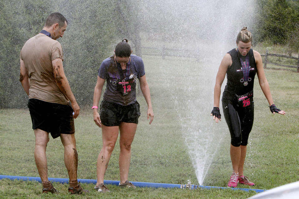David Leibovich, Anna Christensen and Michelle Goodnight rinse off after the Juggernaut mud run in Edmond to raise money to fight breast cancer.