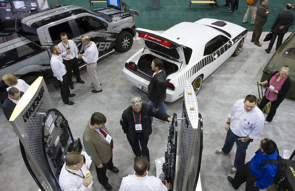 Photo - Attendees of the 2013 International CES consumer electronics show on Wednesday look at products offered by Stillwater-based Kicker at the company's mobile audio booth in Las Vegas.   - PAUL RIEDL