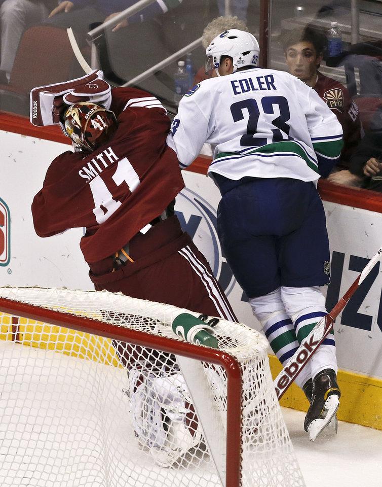 Vancouver Canucks' Alexander Edler (23), of Sweden, knocks Phoenix Coyotes' Mike Smith (41) to the ice, and gets called for a five-minue charging penalty, during the second period in an NHL hockey game, Thursday, March 21, 2013, in Glendale, Ariz. (AP Photo/Ross D. Franklin)